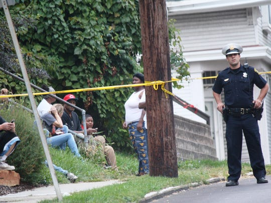 Police and residents alike look out on West Liberty Street, where a man was shot multiple times Tuesday.