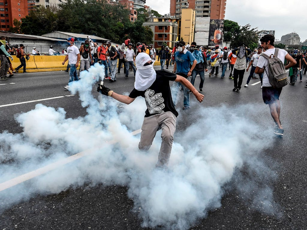 Demonstrators clash with the riot police during a protest against Venezuelan President Nicolas Maduro, in Caracas.\u000d\u000aVenezuelan riot police fired tear gas at groups of protesters seeking to oust Maduro, which have vowed new mass marches afte