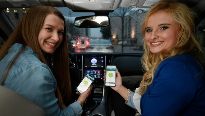 Sammi Jordan (left) and Jansen Donsbach use the app Hytch to carpool and collect cash rewards for sharing their commute to and from work on Feb. 28, 2018, in Nashville.