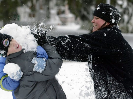 Justin Randall, 9, is hit with a pile of snow by Dee Dee Lee, while taking part in a snowball fight.