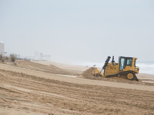 A bulldozer pushes up sand on to the beach at Dewey Beach.