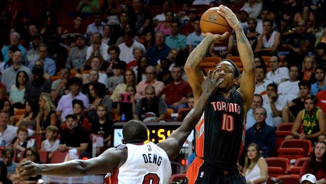 Toronto Raptors guard DeMar DeRozan shoots over Miami Heat forward Luol Deng at American Airlines Arena.