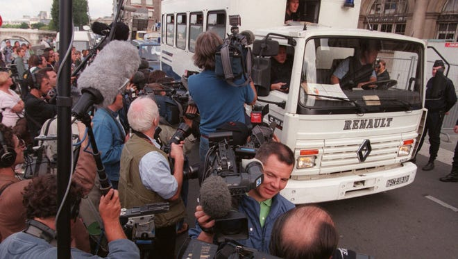 Reporters in Paris gather around police van carrying photographers taken in for questioning in connection with the crash that killed Princess Diana, Sept. 2, 1997.