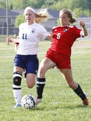Wausau East's Allyson Dehnel, right, takes a shot as Wausau West's Alexa Sheehan defends during Tuesday's Wisconsin Valley Conference girls soccer game Wausau West High School soccer field.