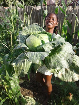 Abigail Nawo, a fourth-grade student at Wilbur Elementary School, shows off her award-winning cabbage.