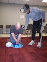 Lee Bongiovi learns CPR as Community Access Unlimited instructor Jonathan Jones looks on. Five CAU members passed a CPR and First Aid Training and became CPR- and first aid-certified.