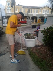 Sunrise Rotarian Bob Hyde cleaning up debris around the fountain.