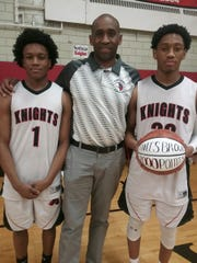 Miles Brown, right, poses with his twin brother, Michael, and father, Michael Brown Sr., after scoring his 2,000th career point in a Section V tournament game Tuesday, Feb. 20.