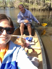 Travel and tourism reporter Leigh Guidry and husband Eric paddle a canoe with their kids in tow on Lake Bistineau.