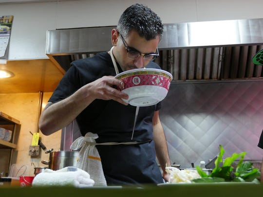 Chef George Azar inspects a bowl of pho at his Flowers of Vietnam pop-up inside Vernor Coney Island in Southwest Detroit on Sunday, March 13, 2016.