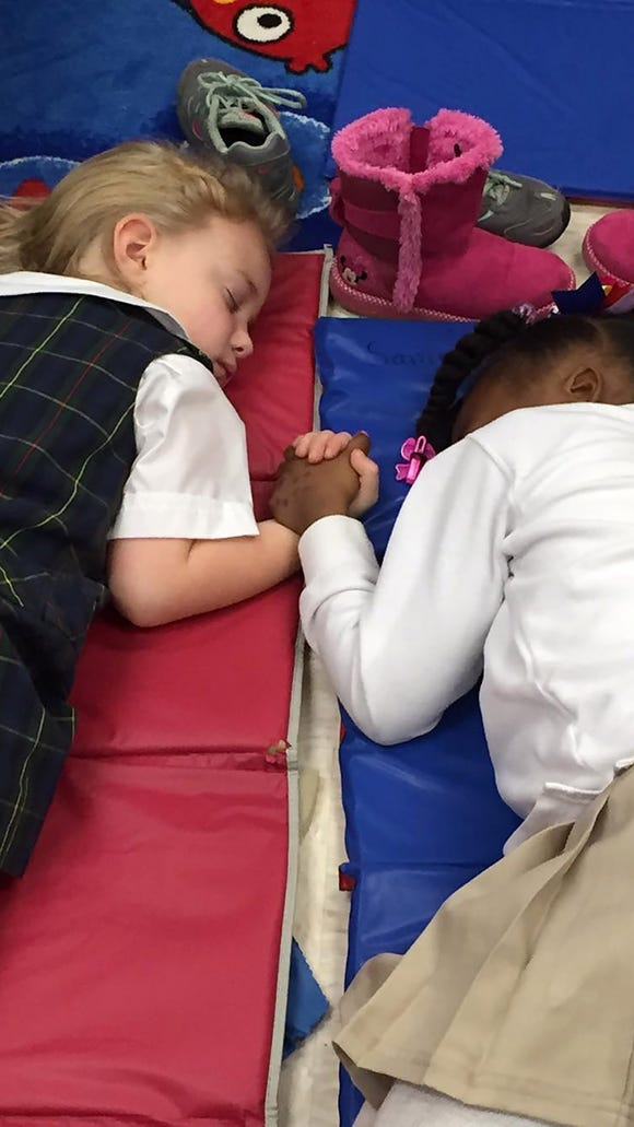 Two girls hold hands during nap time at Presbyterian