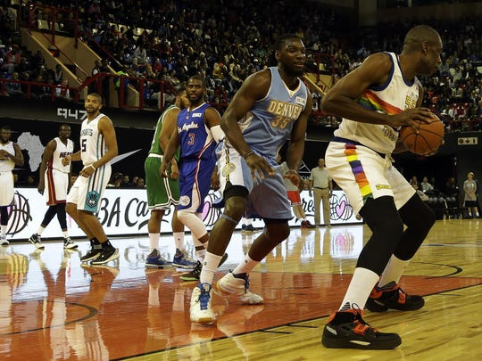 Team Africa's NBA Legend Dikembe Motumbo (right) drives around Kenneth Faried of the Denver Nuggets (second from right) during the NBA Africa Game at Ellis Park Arena in Johannesburg, South Africa.