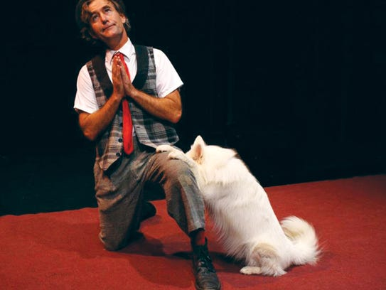 Scott Houghton performs with one of the dogs from Mutts