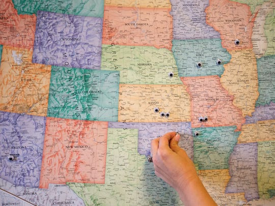 Kas Clegg, co-owner and CMO at Hurts Donut, adds a googly eye onto a map near Tulsa, Oklahoma, marking all of their franchises at the Hurts Donut corporate office in downtown Springfield on Monday, November 28, 2016.