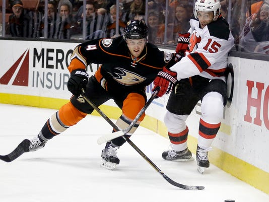 Anaheim Ducks defenseman Cam Fowler, left, battles New Jersey Devils left wing Tuomo Ruutu for the puck during the first period of an NHL hockey game in Anaheim, Calif., Monday, March 14, 2016. (AP Photo/Chris Carlson)