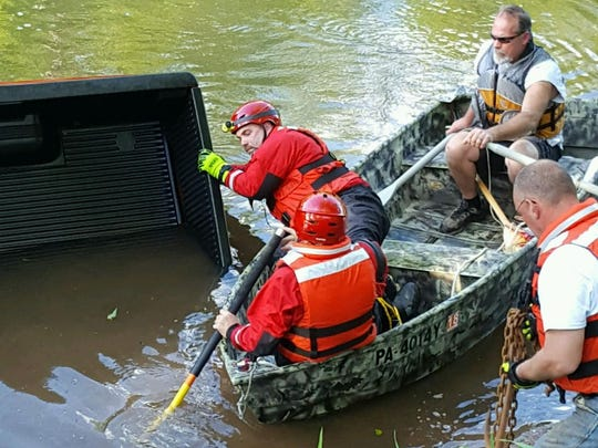 Crews work to pull the pickup out of the creek.