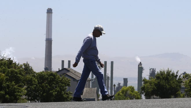 The stacks from the Valero Benicia Refinery are seen as a pedestrian walks in a nearby neighborhood in Benicia. Ontario, Canada, plans to withdrawal from the bi-national cap-and-trade program that linked it with California and Quebec, Canada, in one of the world's largest emissions trading markets.