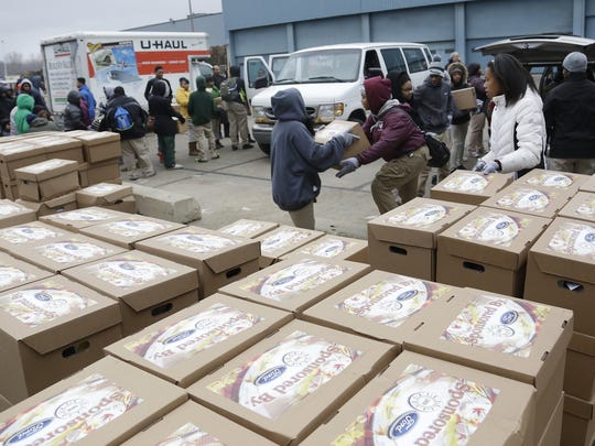 Students from six metro Detroit schools volunteer to load up nearly 16,700 food boxes that included a turkey and trimmings as part of the UAW-Ford Holiday Box of Love Project Thursday Dec. 18, 2014. Mandi Wright/Detroit Free Press