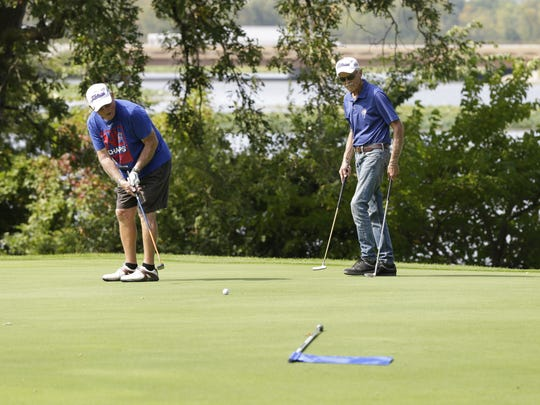 John Harman, right, waits for his brother Jim Harmon to putt Sept. 15, 2017, at Lakeshore Municipal Golf Course.