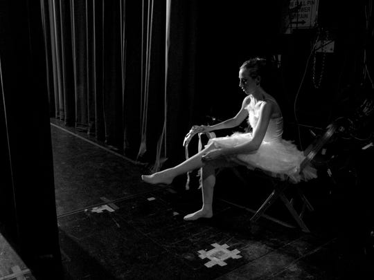 "Dancer Eve Allen takes her pointe shoes off back stage of the Pioneer during rehearsal for A.V.A.'s production of ""Swan Lake."""