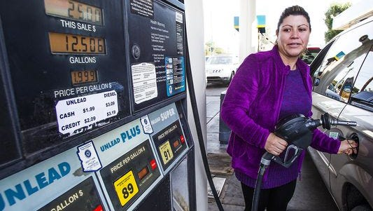 Mariana Godoy puts regular unleaded gas in her van at the Valero gas station near 20th Street and Osborn Road in Phoenix on Dec. 15, 2014.