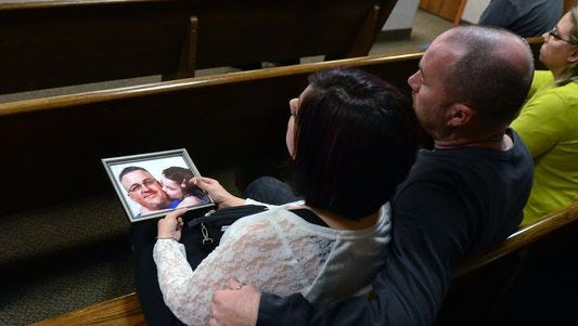 Family members of Timothy Tacie sit with a photo of him and his daughter Monday, March 16, 2015, during the sentencing of Tommy Taylor. Taylor was convicted of operating a vehicle while intoxicated causing death.