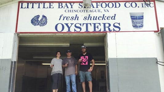 Jenna Chapman (left), Bob Huntley and Josh Chapman stand in front of the Little Bay Seafood Co. sign that will feature prominently in the Black Narrows Brewing Co. interior design.