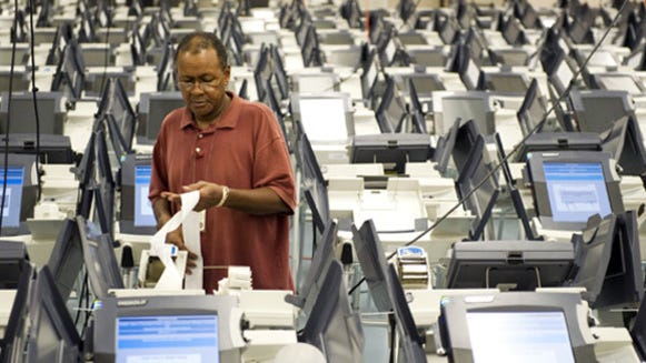 """Assistant voting machine tech Michael Dandridge inspects a """"zero tape"""" from a machine at the Shelby County Election Commission headquarters. Technicians as well as trained auditors inspect each machine to ensure the serial numbers match records, that no votes are currently shown to have been cast, and that voter ID information is accurate."""