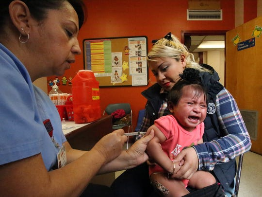 """Maria Lourdes Ramos, a medical assistant at the Henderson Clinic at 721 S. Mesa St., administers a measles, mumps and rubella vaccine to 1-year-old Danna Sofia Torres with help from her mother, Ana Karin Solis. The toddler received a variety of vaccines on both legs and her right arm. Her mother said the vaccines are important for the health of her daughter because """"they prevent sicknesses."""""""