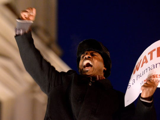 Flint City Council member Wantwaz Davis stands on the steps of the Capitol building to lead chants with the crowd Tuesday, Jan. 19, 2015 at the protest over Governor Rick Snyder's handling of the Flint water crisis, outside the Capitol Building at Governor Snyder's State of the State address. Davis said that he was one of the first to protest the water switch that preceded the the water crisis and that all the state would have had to do to fix this from the start was to spend $100 a day on a corrosive preventive measure for 90 days.