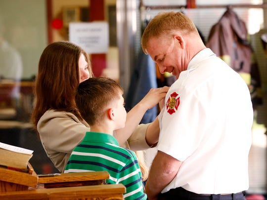 Jill Martino pins the City of Elmira fire chief badge on her husband, Joseph, after he was sworn in on Friday.