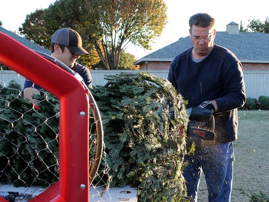 Kevin Kee cuts the end of a Christmas tree Sunday,