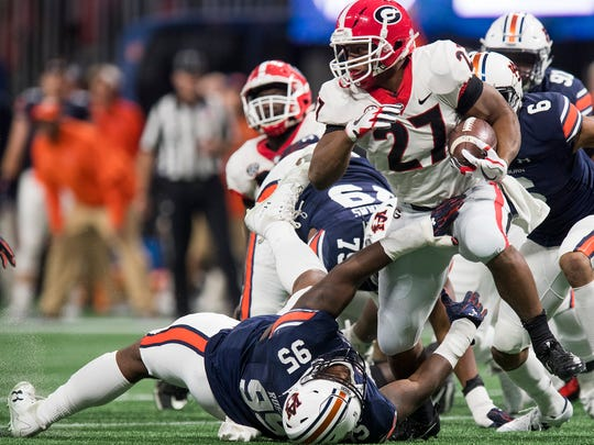 Georgia tailback Nick Chubb (27) slips away from Auburn defensive lineman Dontavius Russell (95) in first half action of the SEC Championship Game at Mercedes-Benz Stadium in Atlanta, Ga. on Saturday December 2, 2017. (Mickey Welsh / Montgomery Advertiser)