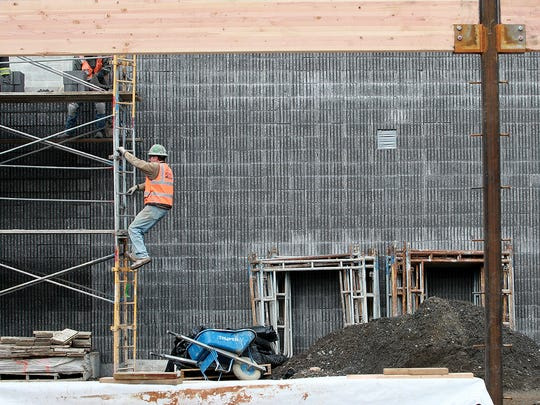 A construction crew member climbs down from the scaffolding while working on the wall of the theater as construction continues at Olympic High School on Wednesday.