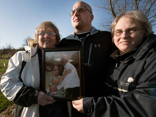 John Barton is joined by his sisters Tammy (Shaffer) Smith, left, and Pam (Shaffer) Cool, on Thursday at the Shaffer family's burial plot in a Waynesboro cemetery. They are holding a photo of their mom, Shirley Shaffer, and their brother, Clinton Shaffer Jr.