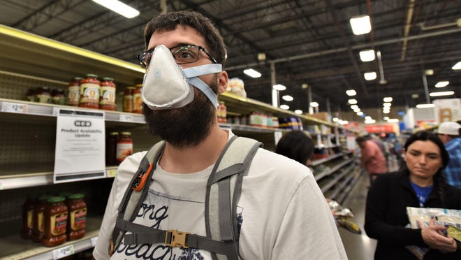 In this file photo, Bastrop resident Bryan Crigger wears a protective mask while shopping at H-E-B in Bastrop.