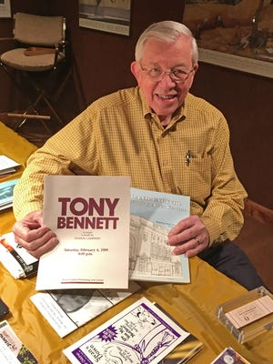 Dr. Benjamin A. Hoover II holds two of the programs from past Strand performances:  Tony Bennett's previous appearance at the Strand and the night Ella Fitzgerald reopened the theater as a performing arts venue.