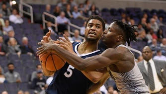 Georgetown guard Jonathan Mulmore, right, fights for the ball against Xavier guard Trevon Bluiett (5) during the first half of an NCAA college basketball game, Wednesday, Feb. 21, 2018, in Washington.