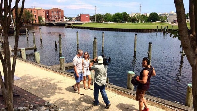 """J.D. and Jenny Schroen (left to right, center) are filmed outside of Brew River Restaurant for their upcoming episode of """"House Hunters."""""""