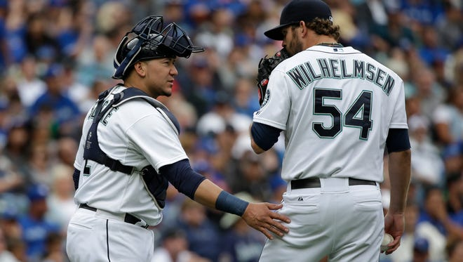 Seattle Mariners catcher Jesus Sucre, left, talks with relief pitcher Tom Wilhelmsen against the Toronto Blue Jays in a baseball game Saturday, July 25, 2015, in Seattle.