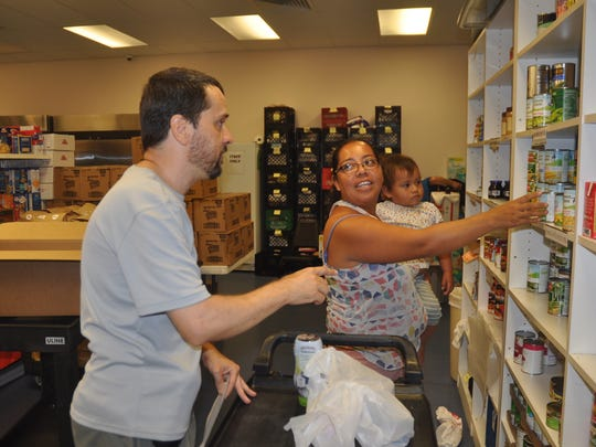 Aurelia Santiago and her son Adrian, 21 months, get supplies at the Bonita Springs Assistance Office. Andy Ruffalski, a program assistant there, helps her.