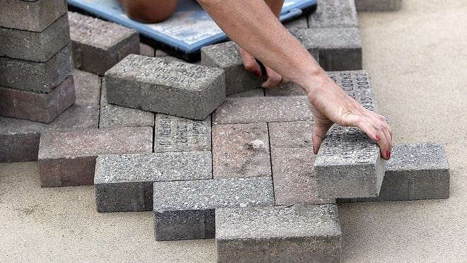 Heather Pierce from Sticks n' Stones Landscaping places a paver brick in the memorial walkway at the new Hospice of North Central Ohio offices on Dauch Drive on Tuesday.
