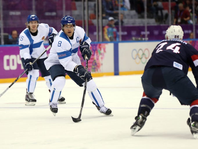 Finland forward Teemu Selanne (8) controls the puck as USA forward Ryan Callahan (24) looks on in the men's ice hockey bronze-medal at the 2014 Olympics in Sochi, Russia.