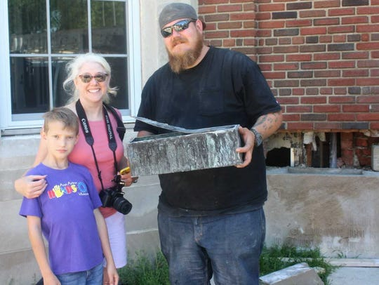 Ron Jarvis (right) is pictured holding the metal box/time capsule he found embedded in a block of cement near the front of the school. Also pictured are Wendy Harless and her son Holden.