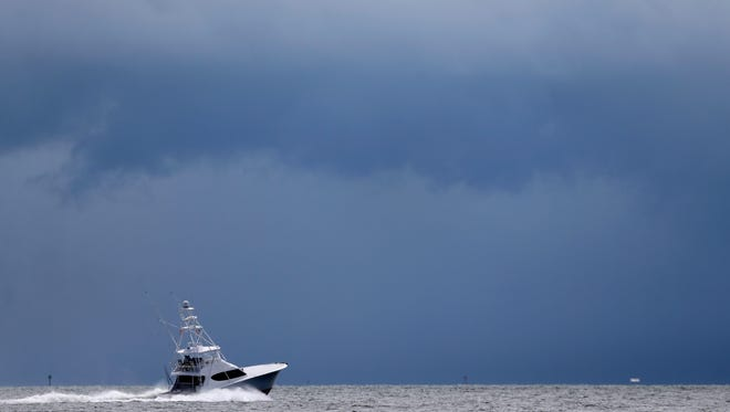 In this Sept. 12, 2014 file photo, a fishing boat heads out to the Atlantic Ocean near Miami as dark clouds loom in the distance. In the annual detailed physical for Earth's climate, scientists noted the world is in increasingly hot and rising water. The National Oceanic and Atmospheric Administration and the American Meteorological Society's annual state of the climate delved into the hot details of already reported record-smashing warmth globally in 2014, giving special attention to the world's oceans.