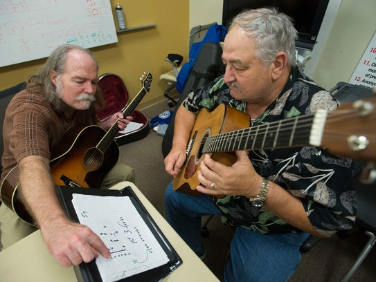 Guitar teacher, Douglas Morgan, left, gives veteran
