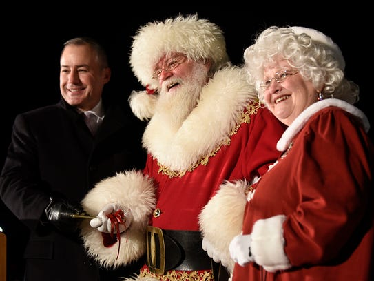 Mayor William Wild presents Santa and Mrs. Claus the