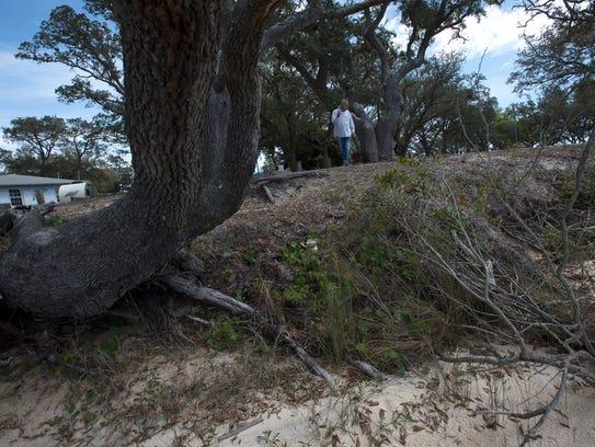 Navy Point resident, Barry Hoppe, surveys the erosion