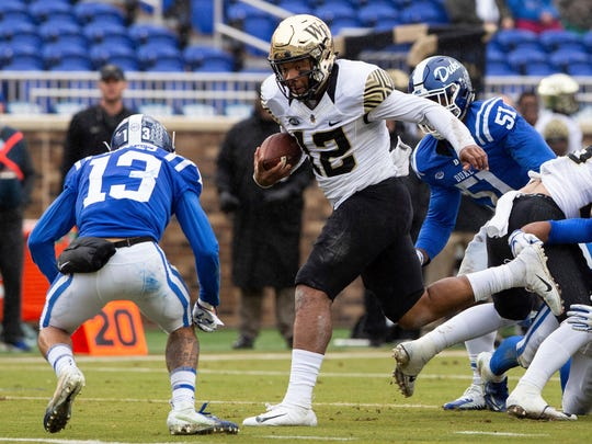 Wake Forest quarterback Jamie Newman (12) carries the ball ahead of Duke's Jordan Hayes (13).