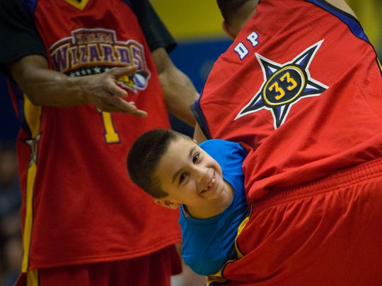 Two Wizard players wrestle for Anthony M., 8, during a prank. The Harlem Wizards played against a combination team of Lyndhurst principals, teachers, cops and coaches at a special Police Unity Tour fundraiser on Sunday, Feb. 26.